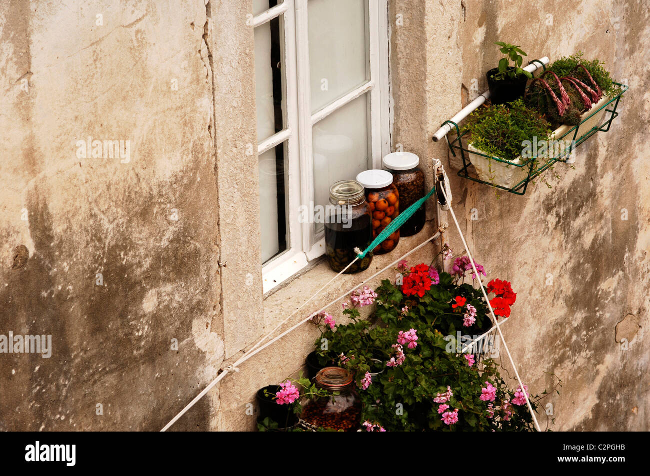 Jars of fruit with geranium and herb window boxes on a residential property, Dubrovnik, Croatia. - Stock Image