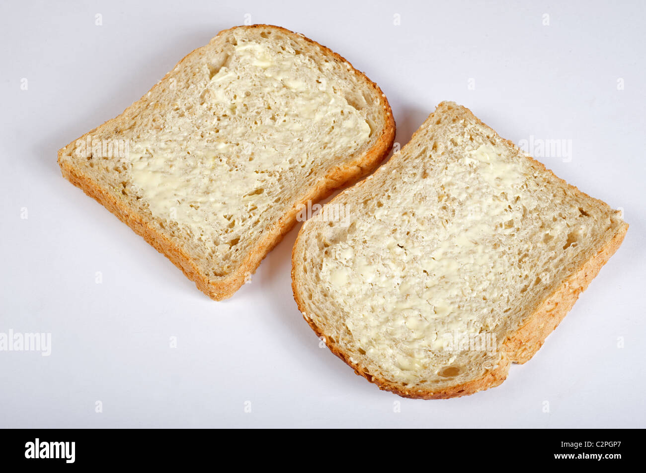 Buttered slices of Hovis hearty oat bread - Stock Image