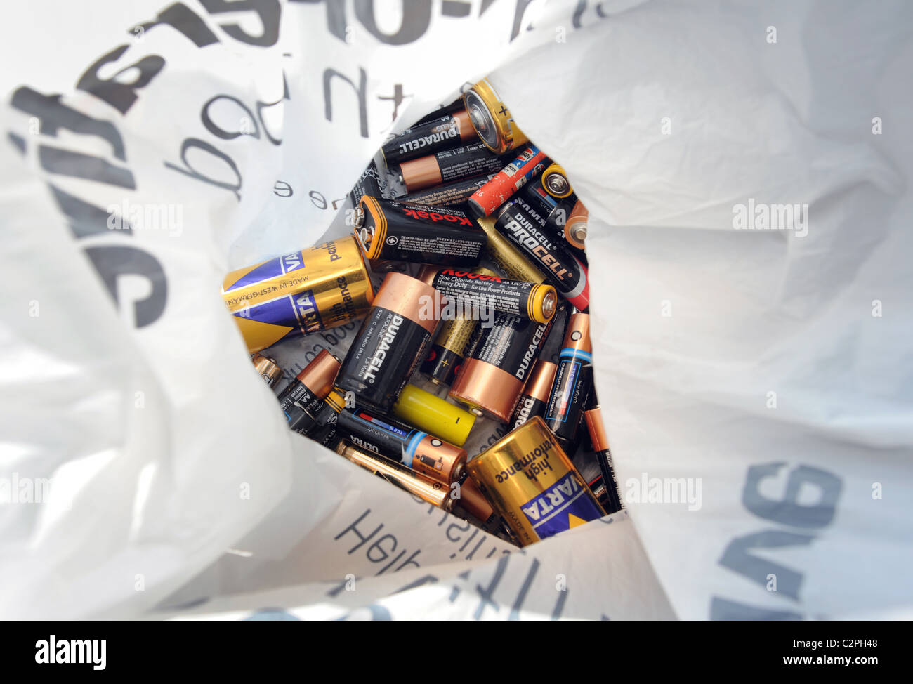 USED BATTERIES IN PLASTIC CARRIER BAG READY TO BE RECYCLED RE RECYCLING RECYCLE ENERGY ELECTRICAL GREEN ETC UK - Stock Image