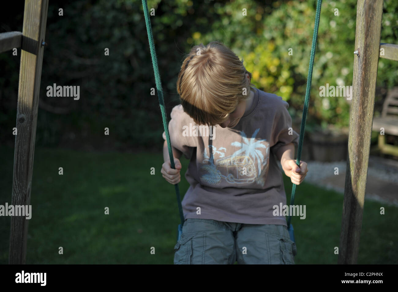 A young fair haired boy sitting on a garden swing with his head down looking