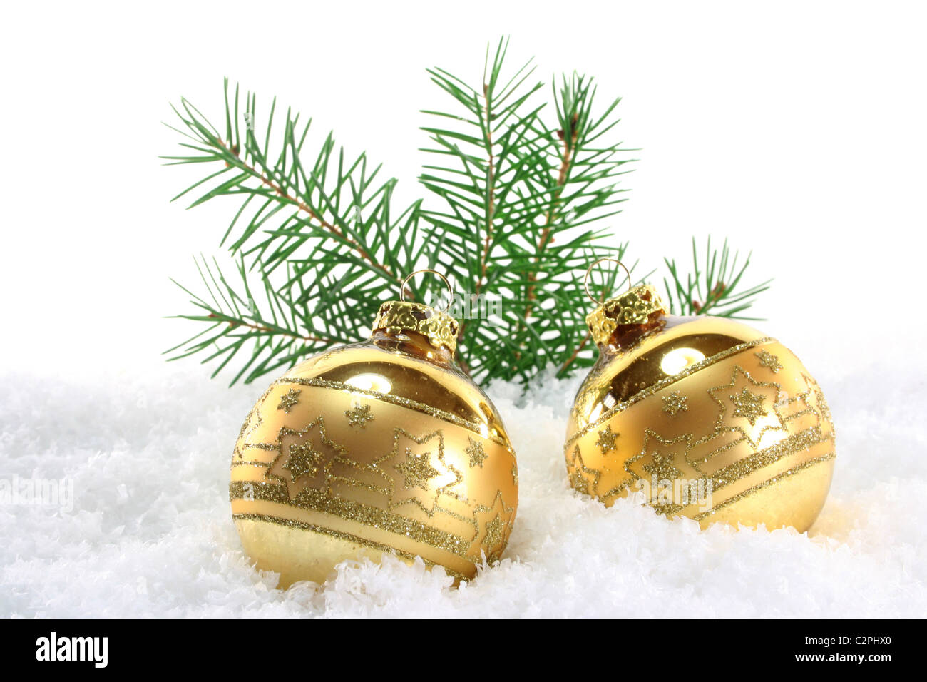 one golden Christmas ball with pine branches lies in the snow - Stock Image