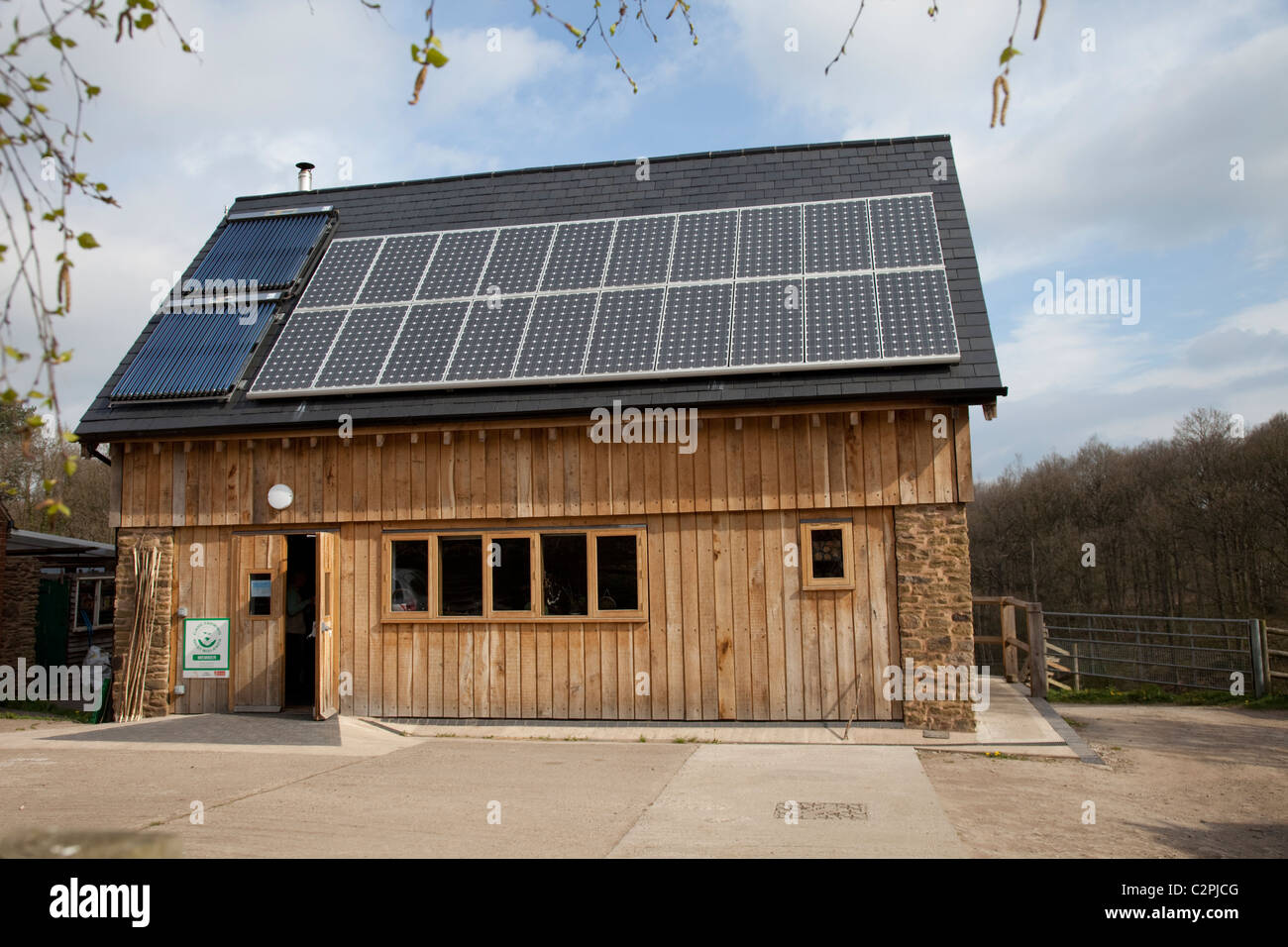 Solar thermal and PV panels on roof of sustainable oak timber building Ruskin Studio Wyre Forest Bewdley UK - Stock Image