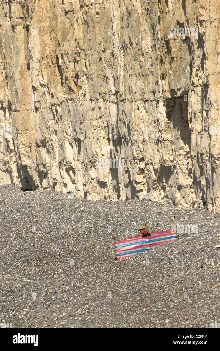 Windbreak and beach goer at Birling Gap in the South Downs National Park. - Stock Image