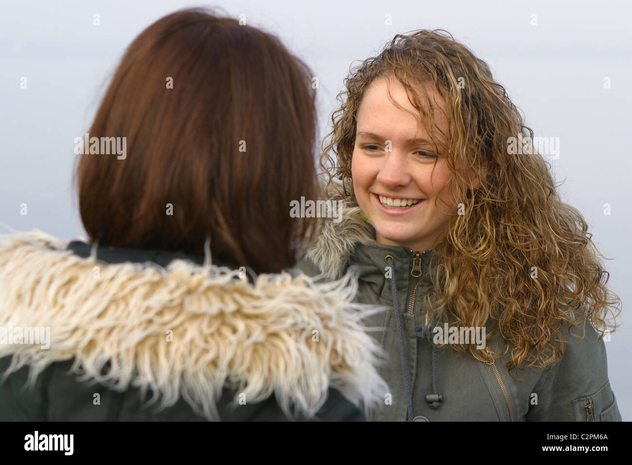 Two young women chatting outside in winter coats - Stock Image