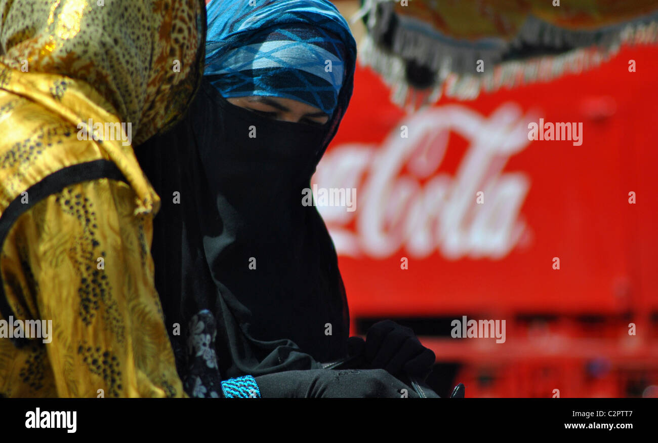 Arab women in burqas in front of a Coca Cola truck in Morocco - Stock Image