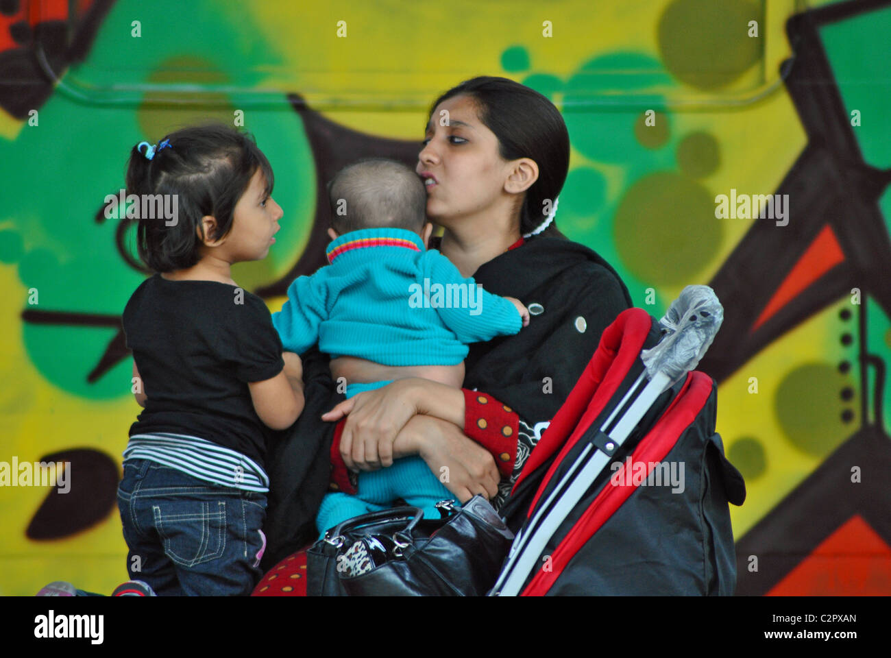 Single mother with two children against backdrop of graffiti, Venice, Italy - Stock Image