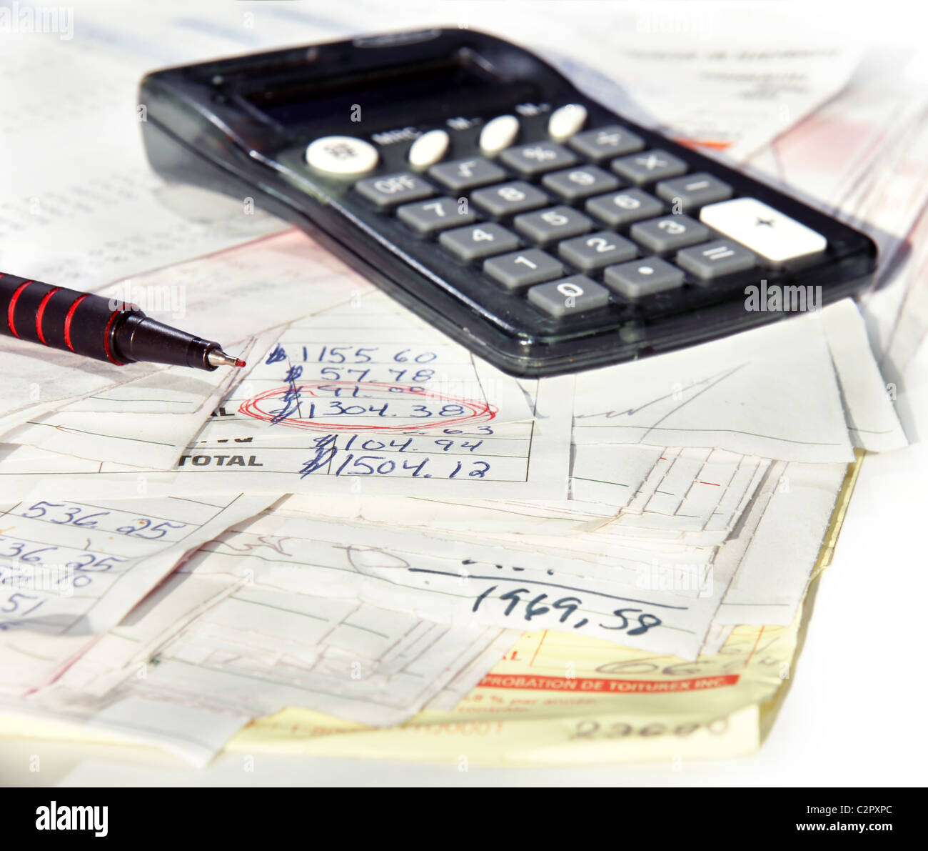 Adding the bills, calculator and real invoices with red tip pen and circled amount of reno costs. - Stock Image