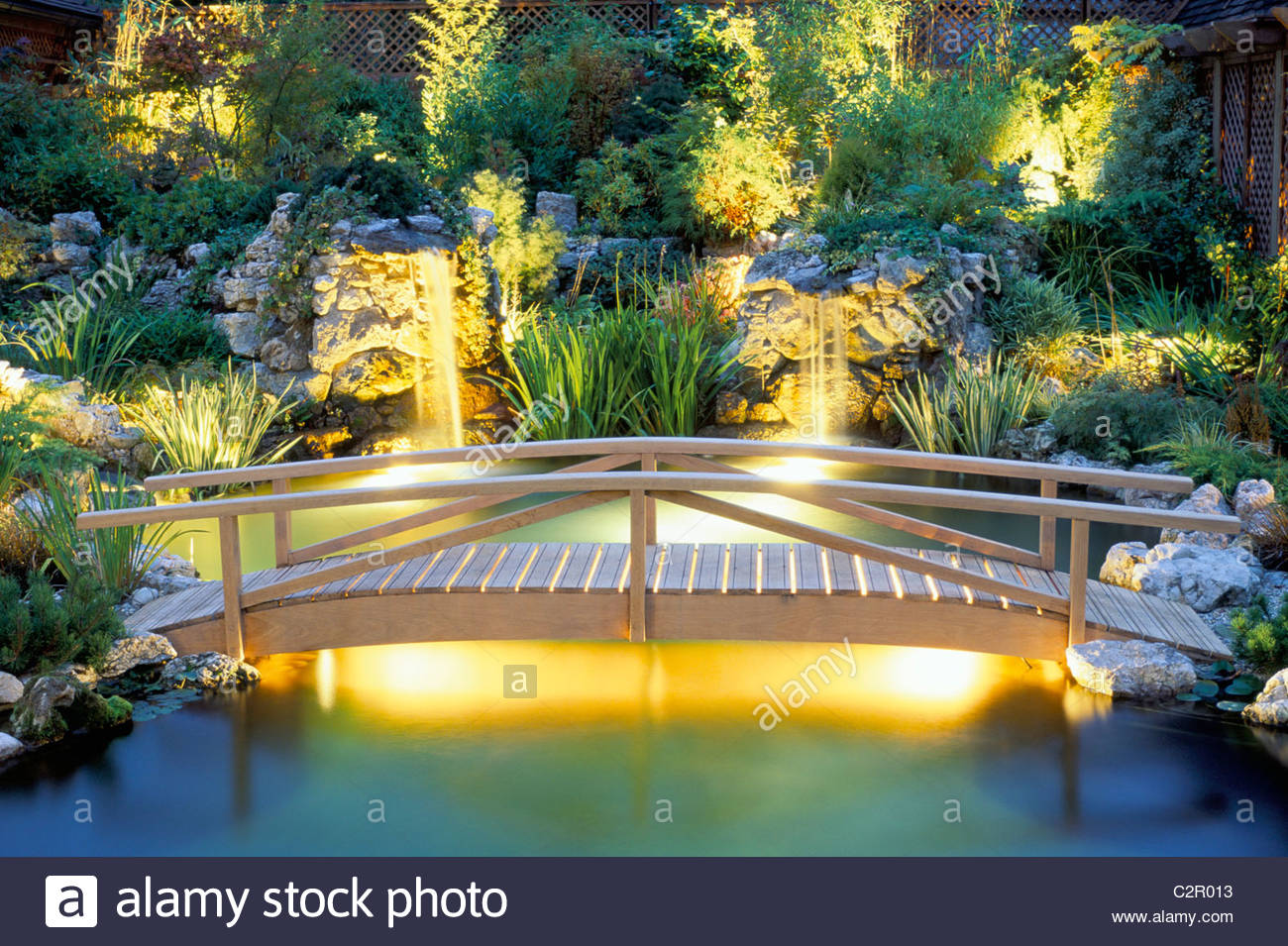 Wooden Bridge Over Koi Pond.lighting By Garden And Security Lighting.  Design By Natural And Oriental Water Gardens