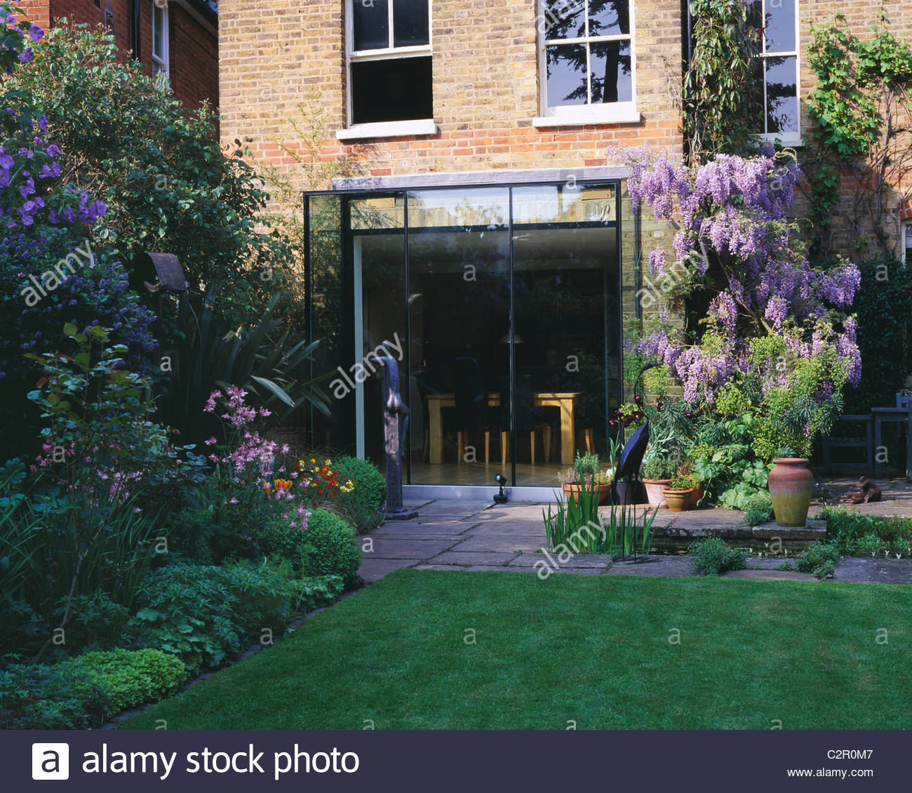 view of lawn and back of house with rectangular pool, wisteria, glass fronted kitchen and sculpture by Helen Sinclair - Stock Image