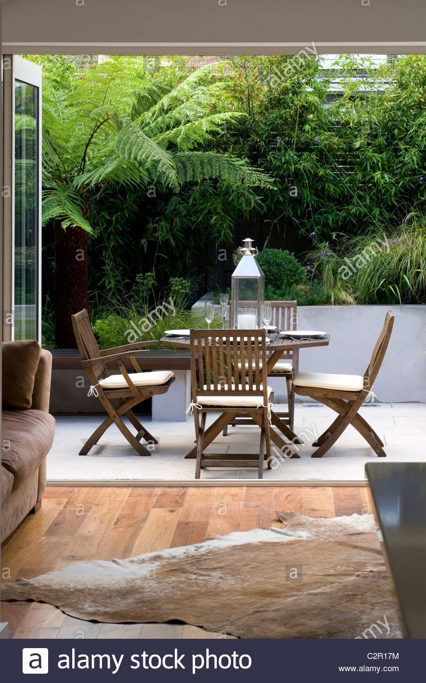 Small town garden with patio with raised beds, tree fern and table ...
