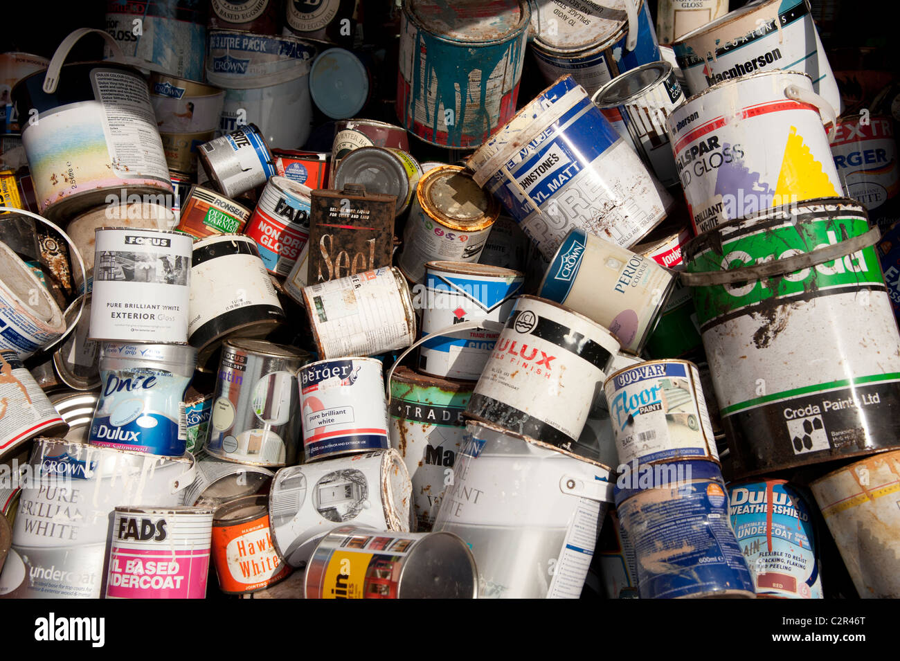 a pile of old battered pots of household paint at a local authority waste recycling centre, Wales UK - Stock Image