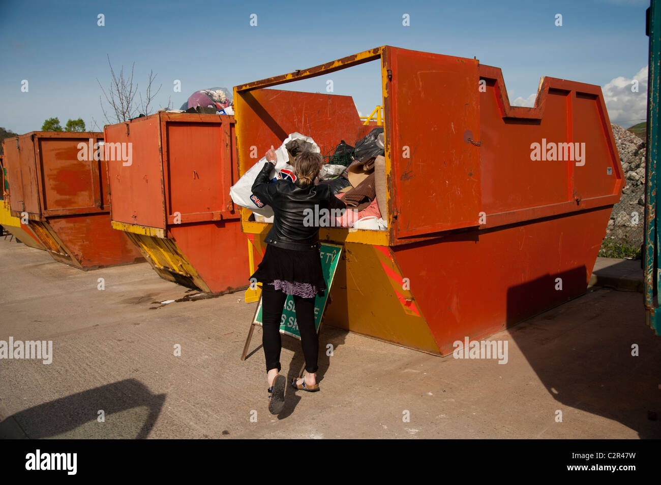 A woman dumping her domestic rubbish at a local authority waste recycling centre, Wales UK - Stock Image