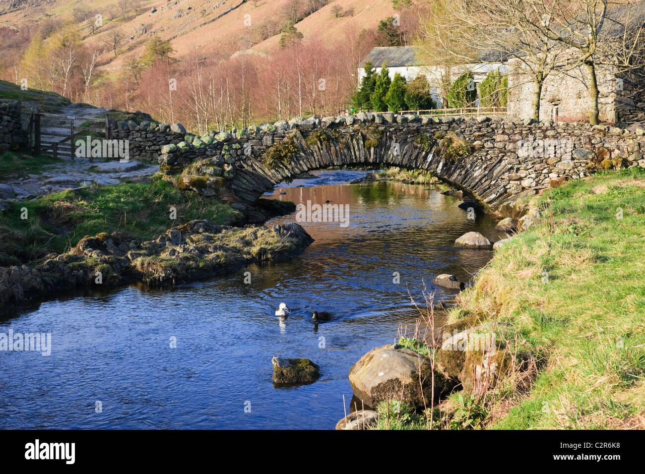 Quaint old packhorse bridge over Watendlath Beck in the Lake District National Park. Watendlath, Cumbria, England, - Stock Image