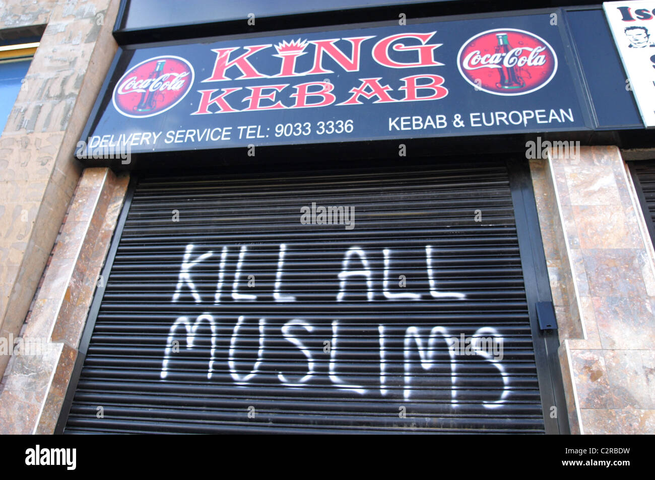 kill all muslims racist graffiti on a kebab shop security shutter in belfast in the uk - Stock Image