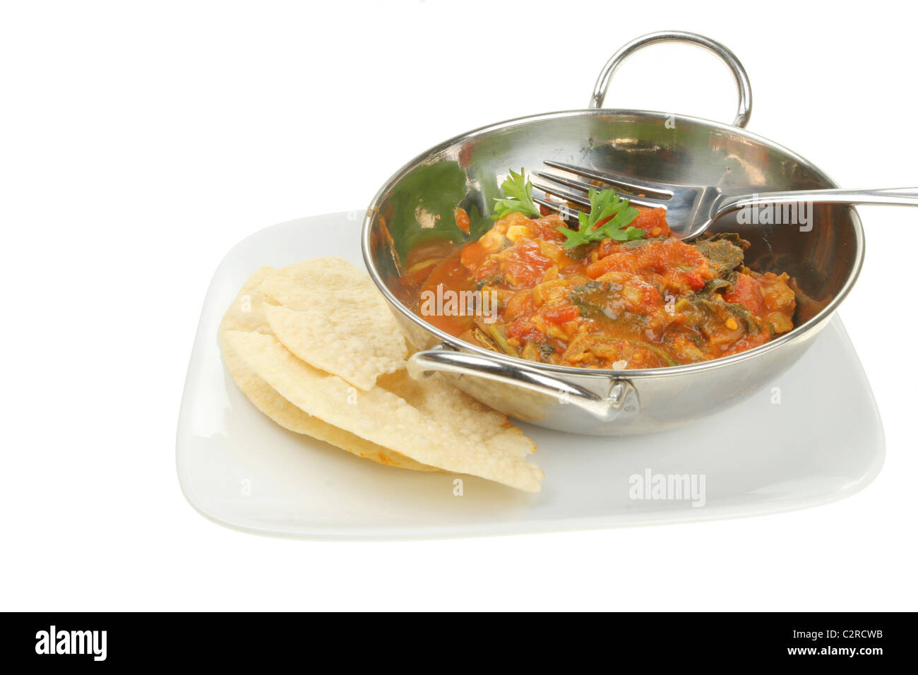 Curry and puppodoms on a plate isolated against white - Stock Image