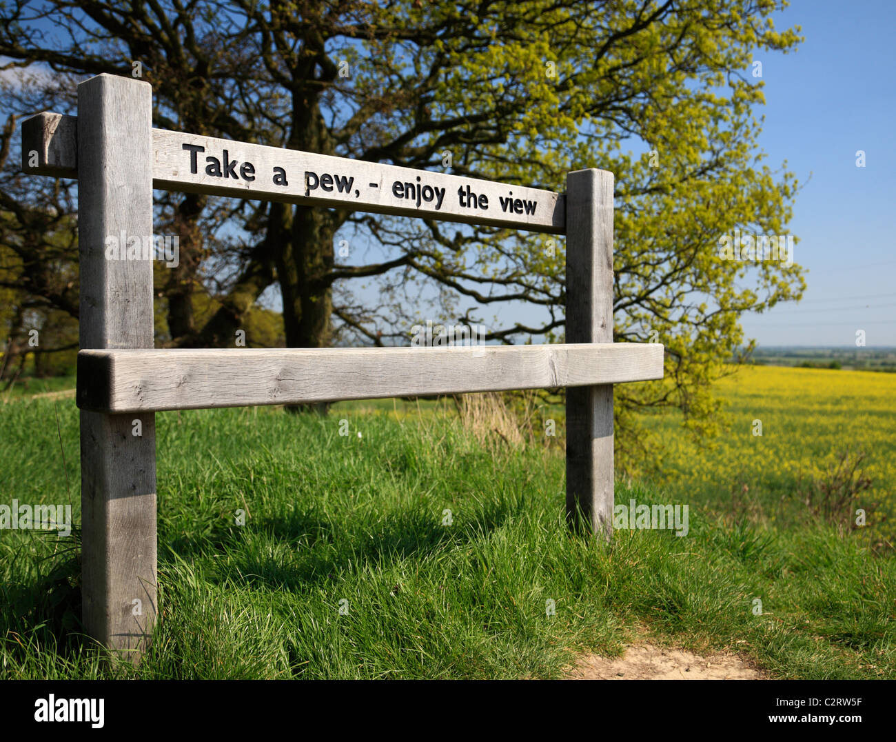 Rural bench with a message, Take a pew, enjoy the view . - Stock Image