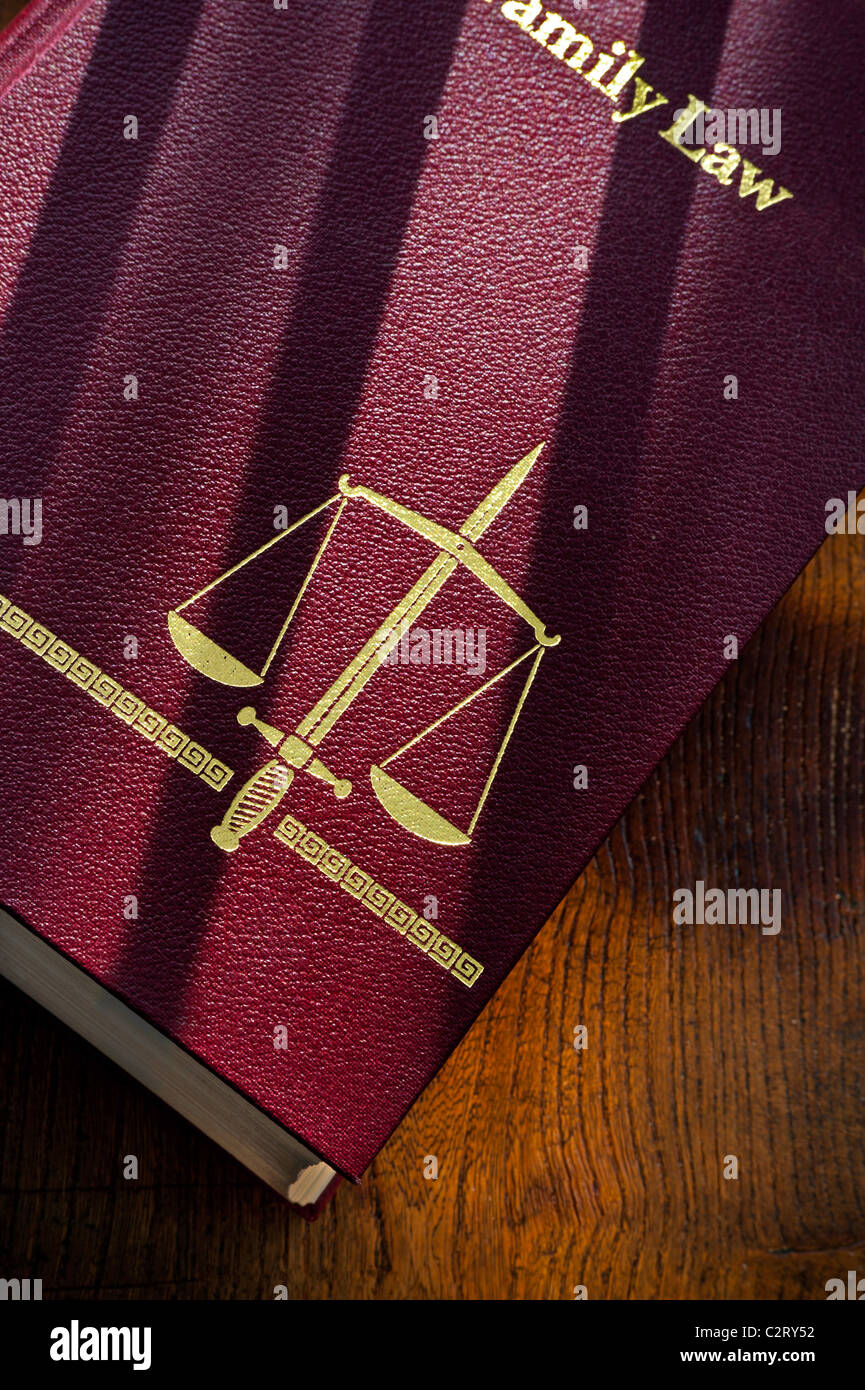 Law concept  Family Law book with scales of justice and double edged sword motif with shadows of bars glancing on - Stock Image
