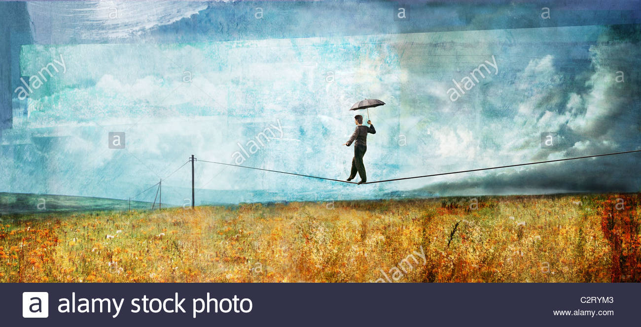 Man with umbrella walking on tightrope telephone wire - Stock Image