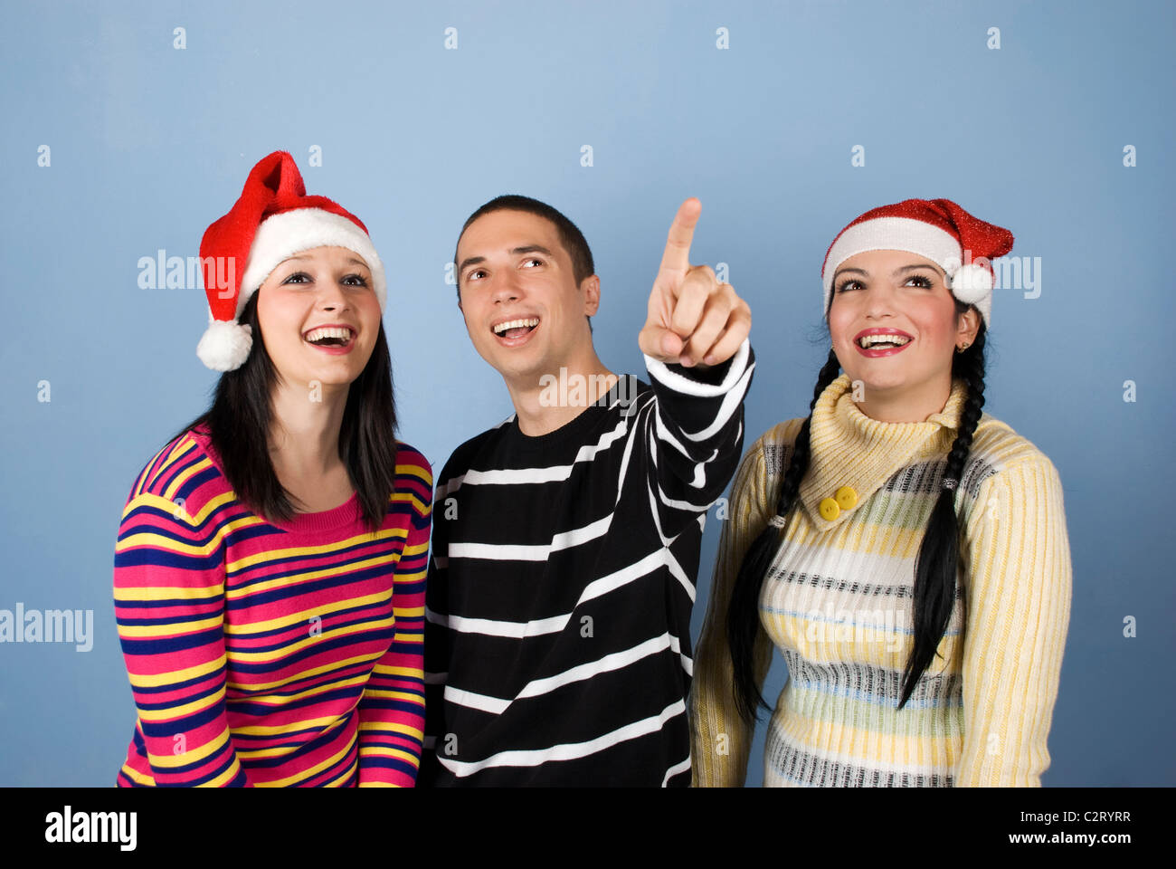 5ccf95993 Happy young Christmas friends people with Santa hats laughing Stock ...