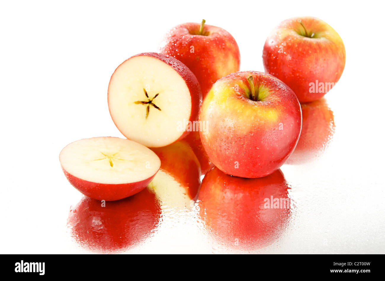 Group of wet apples on the mirror with white background. One apple is cut in half crosswise and the pentagram is - Stock Image