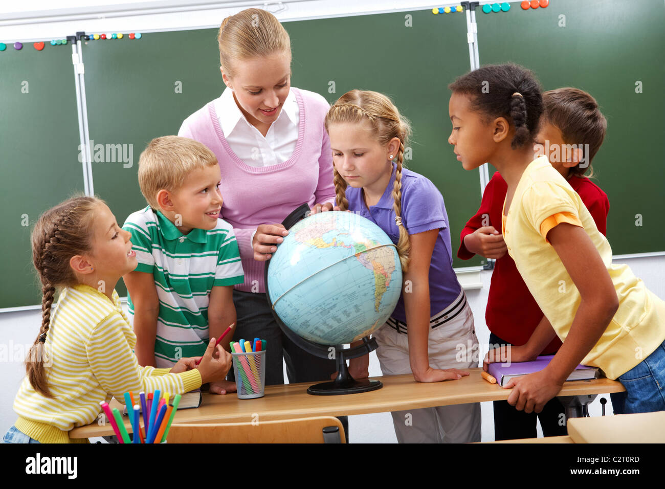 Portrait of pupils looking at globe while listening to teacher during geography lesson - Stock Image