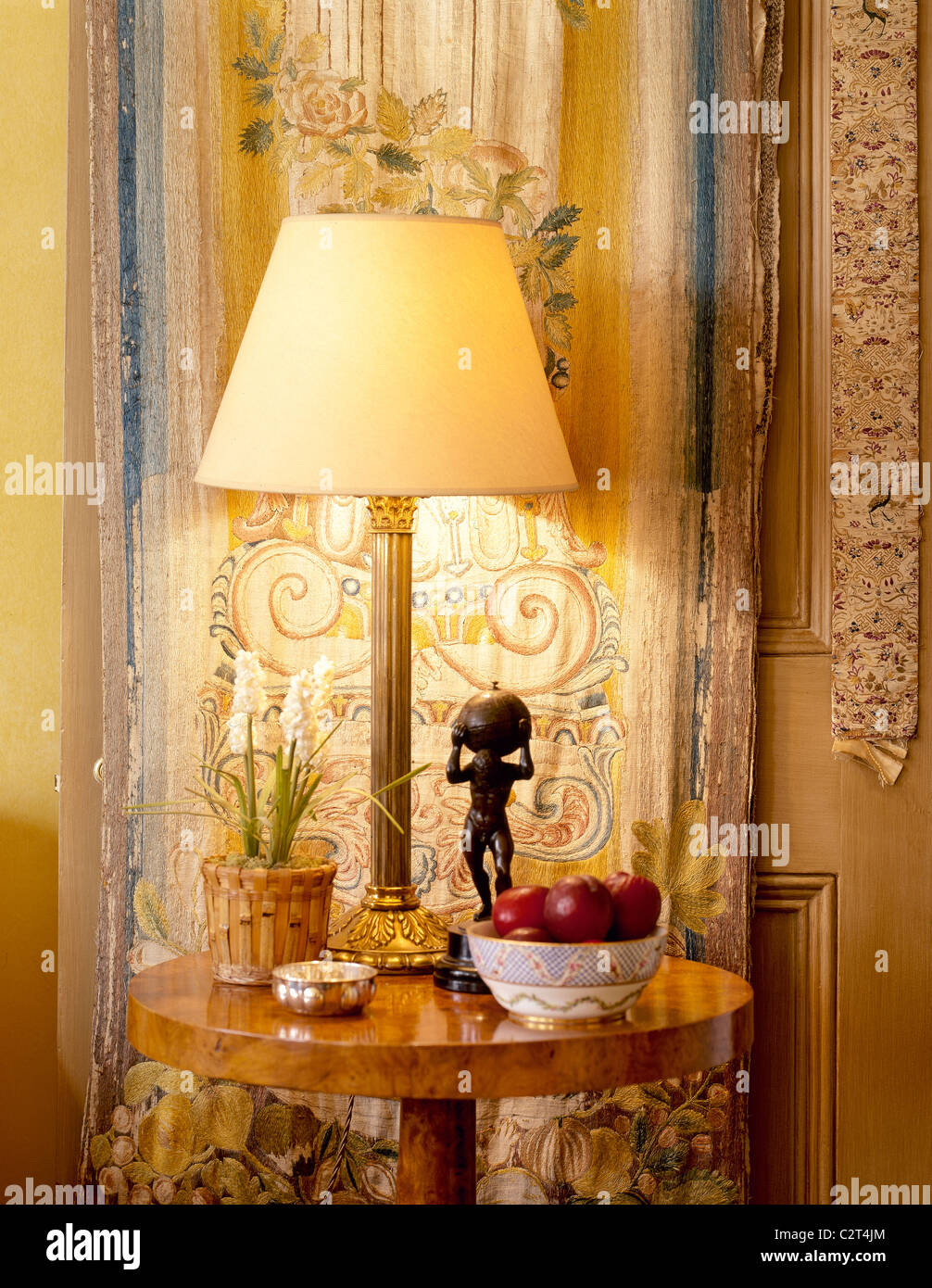 polished wood, round occasional table, gilt lamp - Stock Image