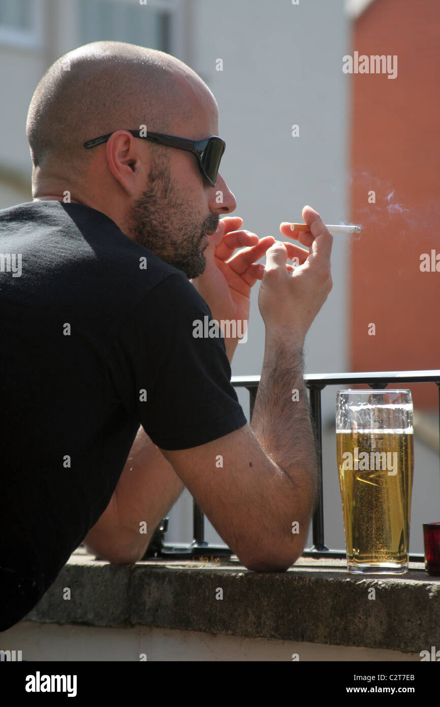 Young man smoking and drinking - Stock Image