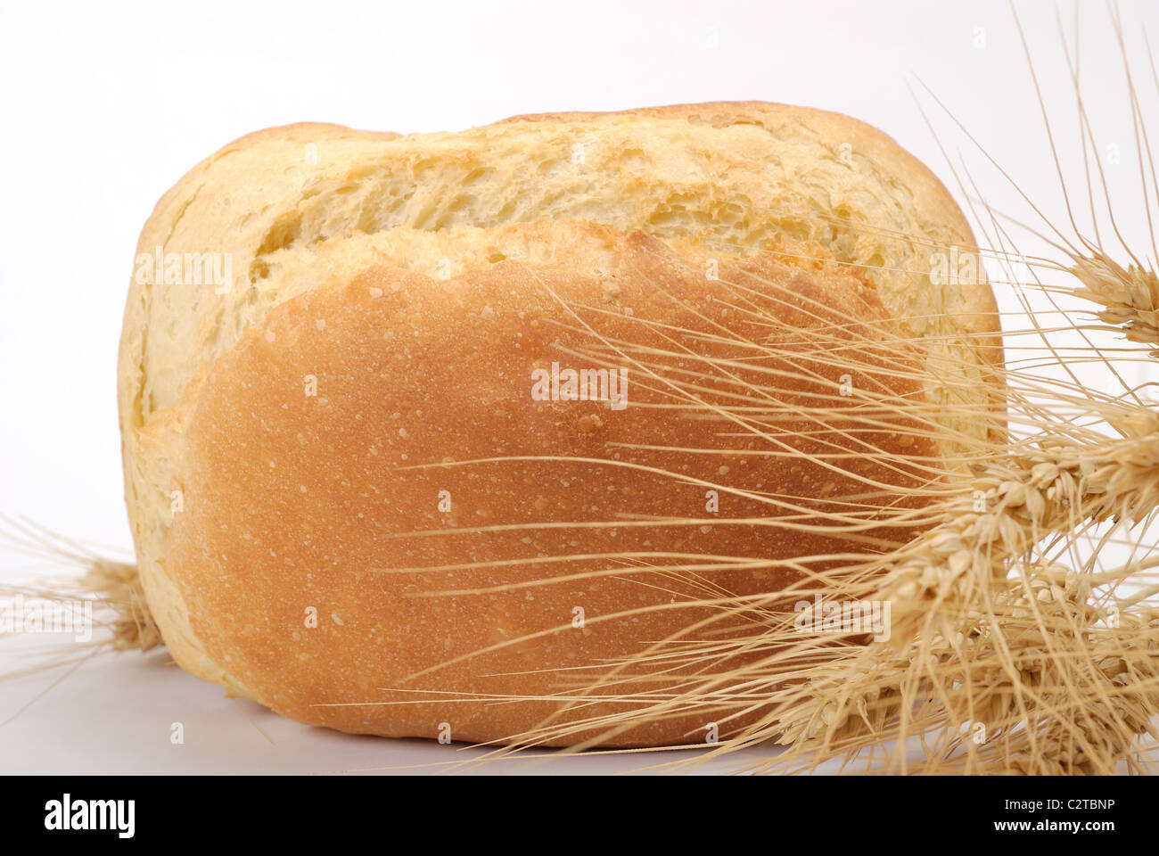 rosy loaf of bread with wheat ears - Stock Image