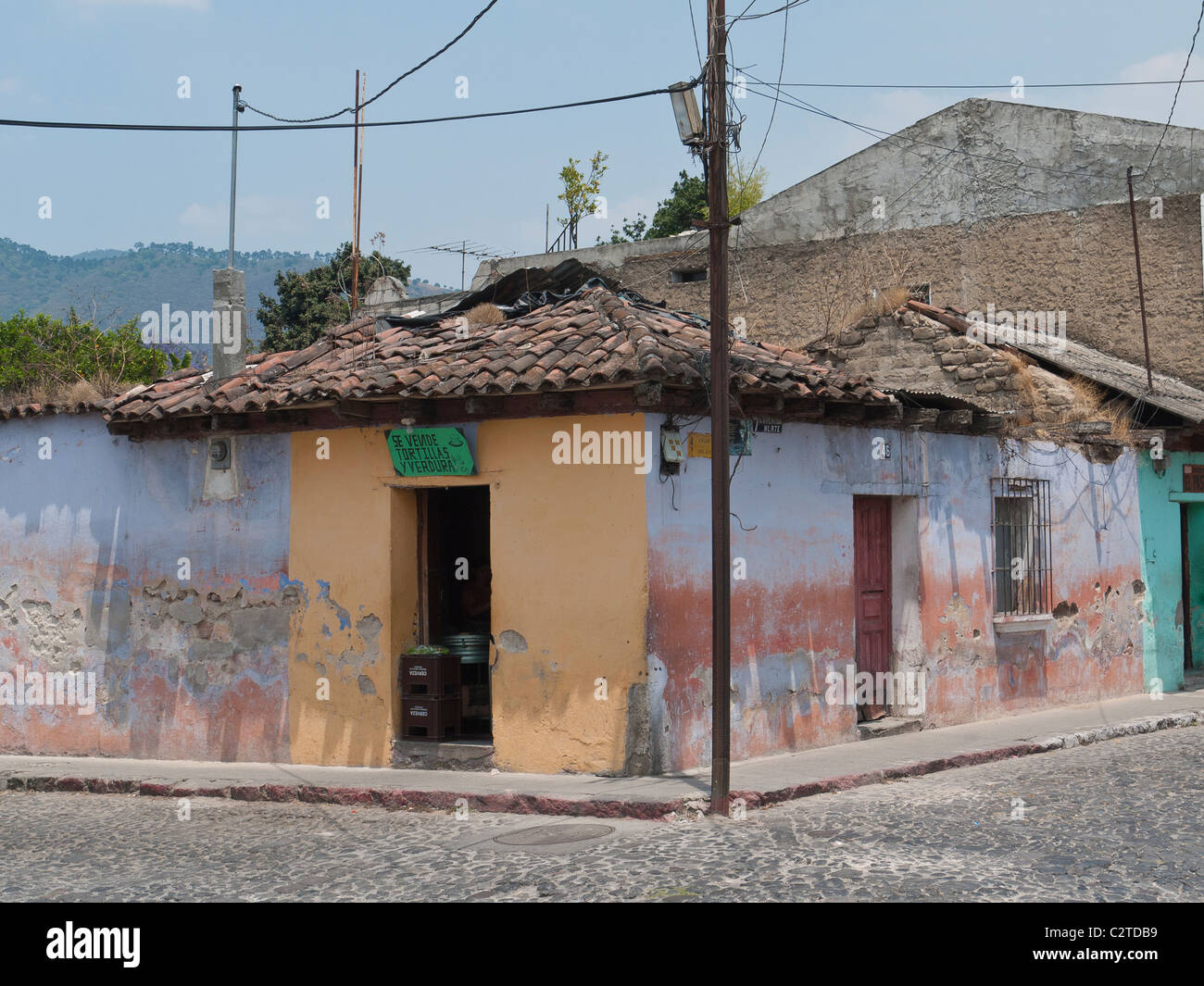 A typical multicolored building sits on a corner n the Spanish colonial city of Antigua, Guatemala. - Stock Image