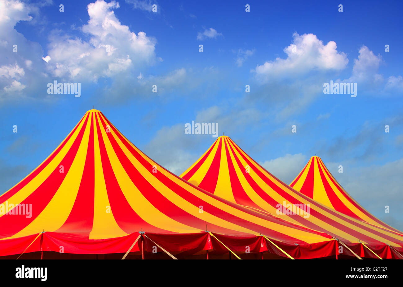 Circus tent red orange and yellow stripped pattern blue sky - Stock Image