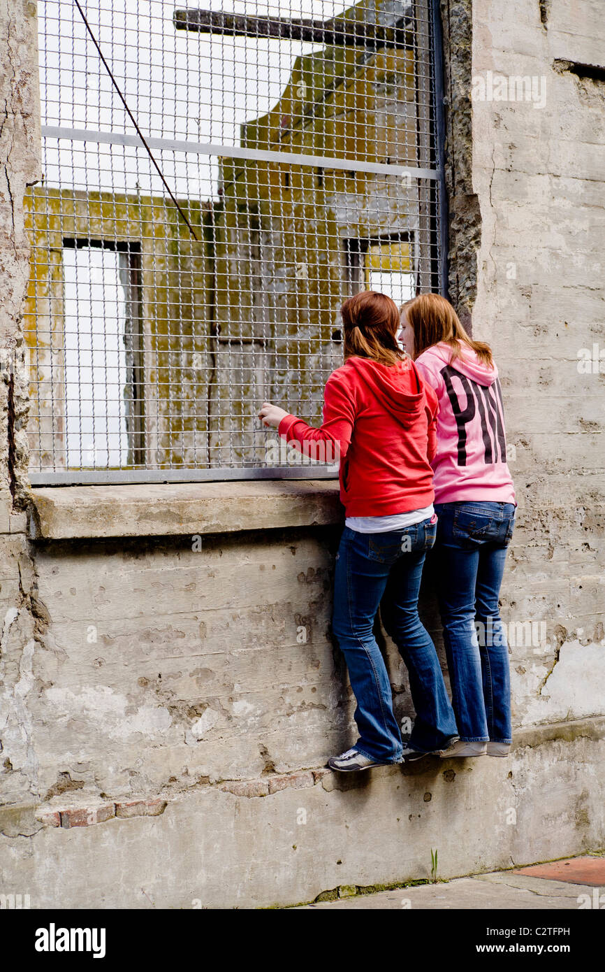 Two visitors peer into the ruins of the officers club building at the former Alcatraz Federal Prison,  now a tourist - Stock Image