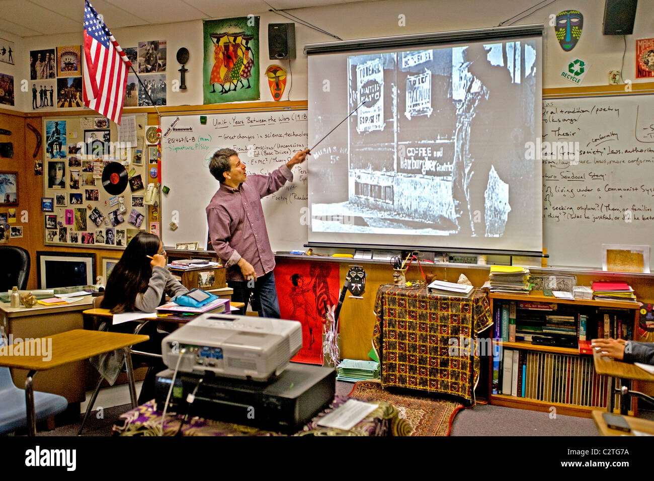 A history teacher uses a liquid crystal display (LCD) projector while lecturing to his class on the Great Depression. - Stock Image