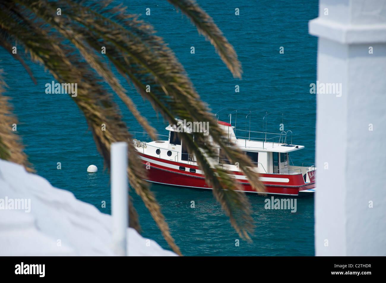 Boat moored in Hamilton Harbour, Hamilton, Bermuda - building in foreground. - Stock Image