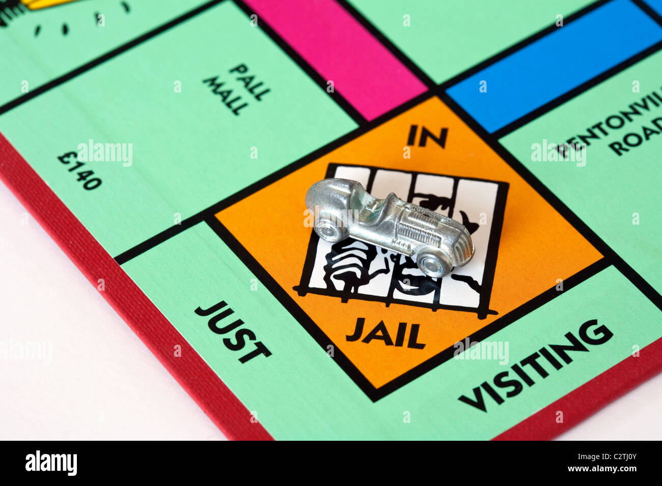 A car piece in Jail on a monopoly game board UK - Stock Image