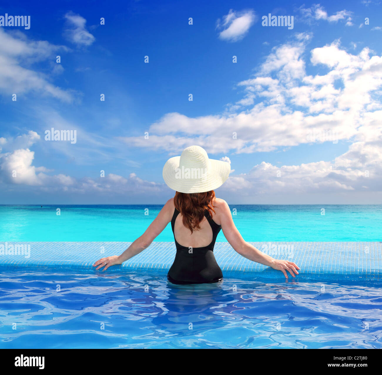 Caribbean tropical sea view from blue pool rear woman beach hat - Stock Image