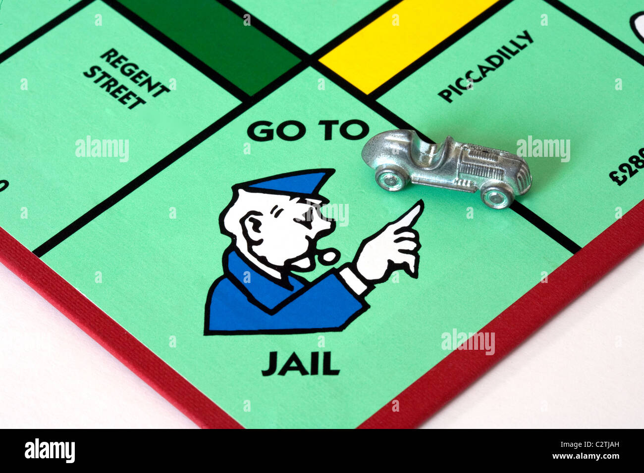 A car on the 'Go to Jail' space on a monopoly game board UK - Stock Image