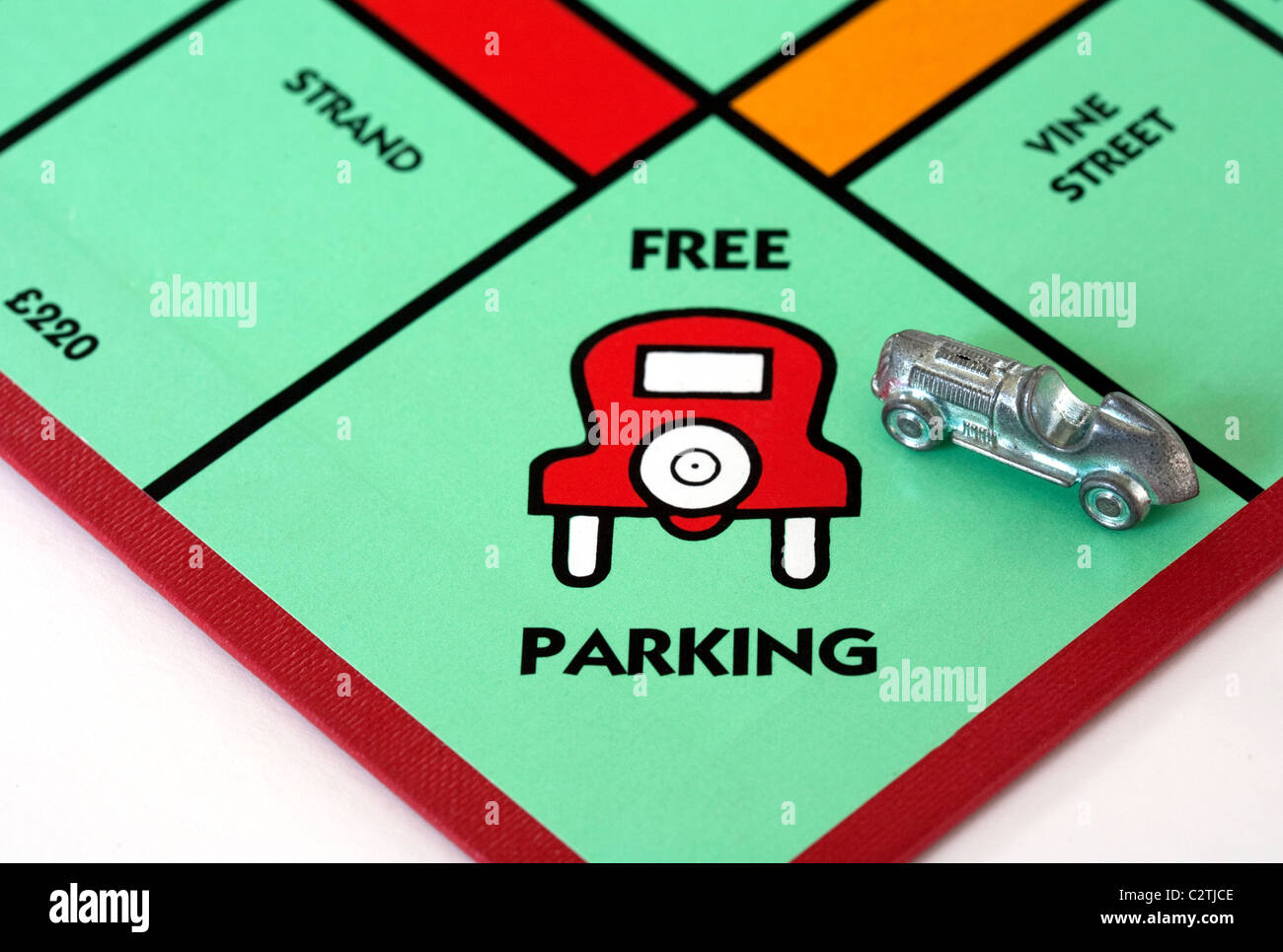 A car on the 'Free Parking' space on a monopoly game board UK - Stock Image