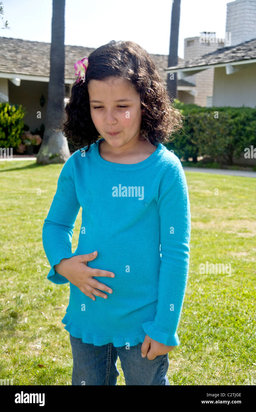 A five-year-old Egyptian-American girl winces with pain from a stomachache outdoors in Laguna Niguel, CA. Stock Photo