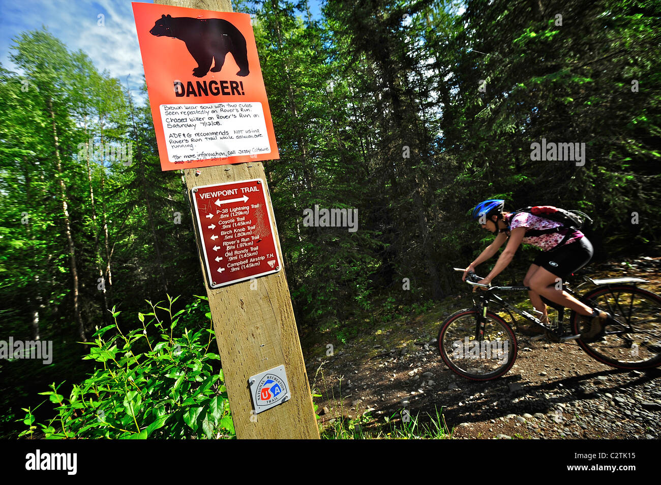Woman rides by a bear warning sign on the Viewpoint Trail near Campbell Airstrip in Bicentennial Park, Anchorage, - Stock Image