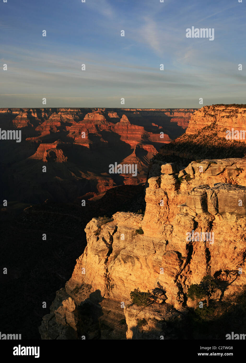 vertical image from the South Rim of the Grand Canyon with only a few of the formations lit by the evening light - Stock Image