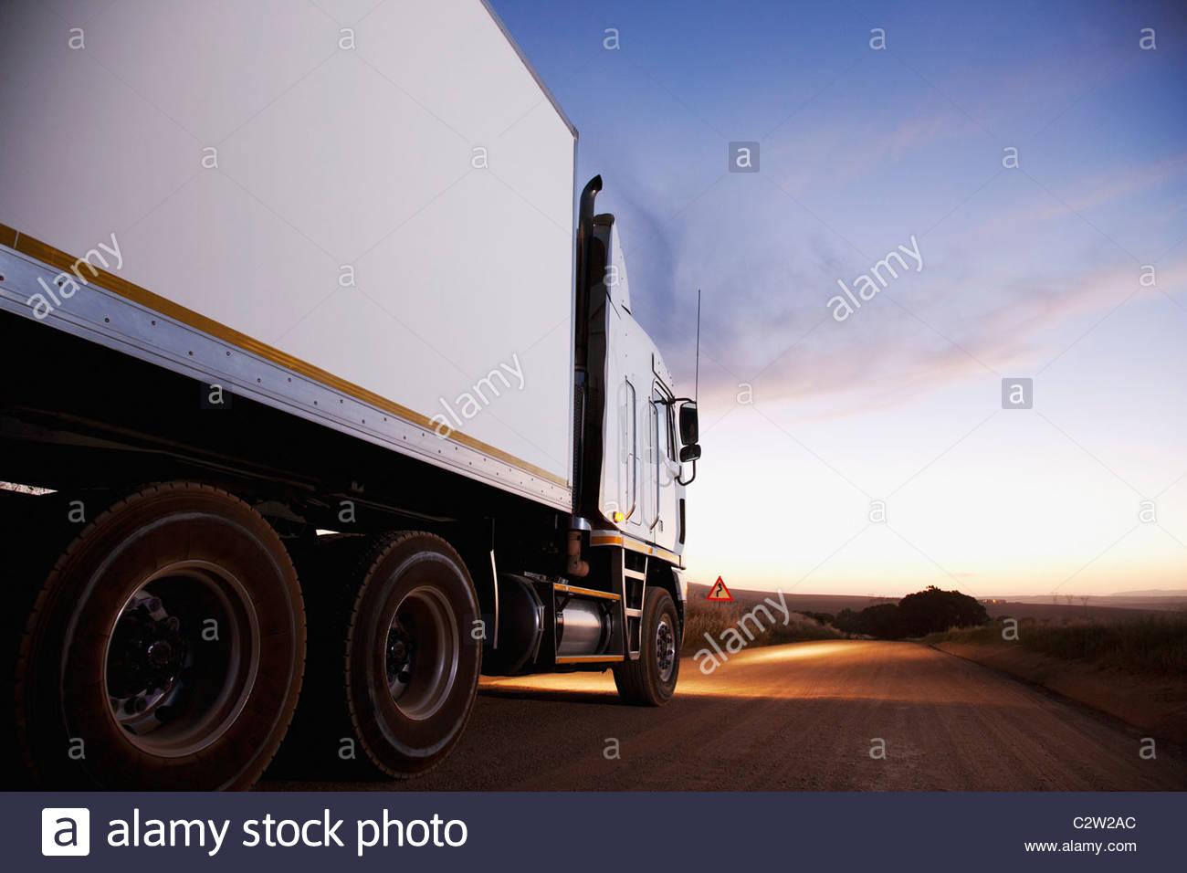 Semi-truck driving on dirt road - Stock Image
