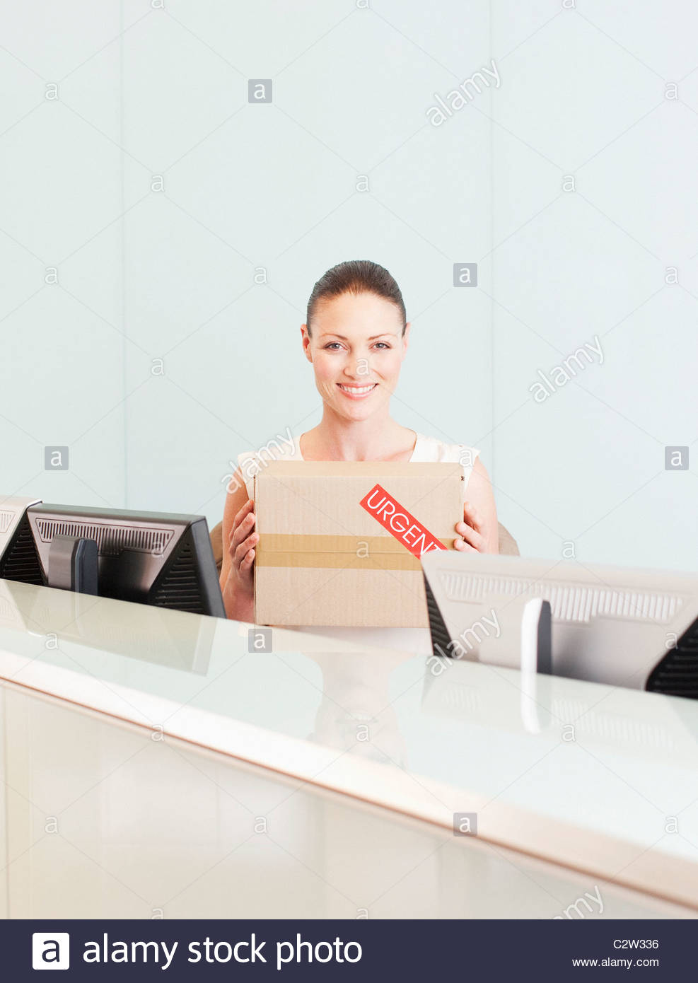 Receptionist holding box marked urgent Stock Photo