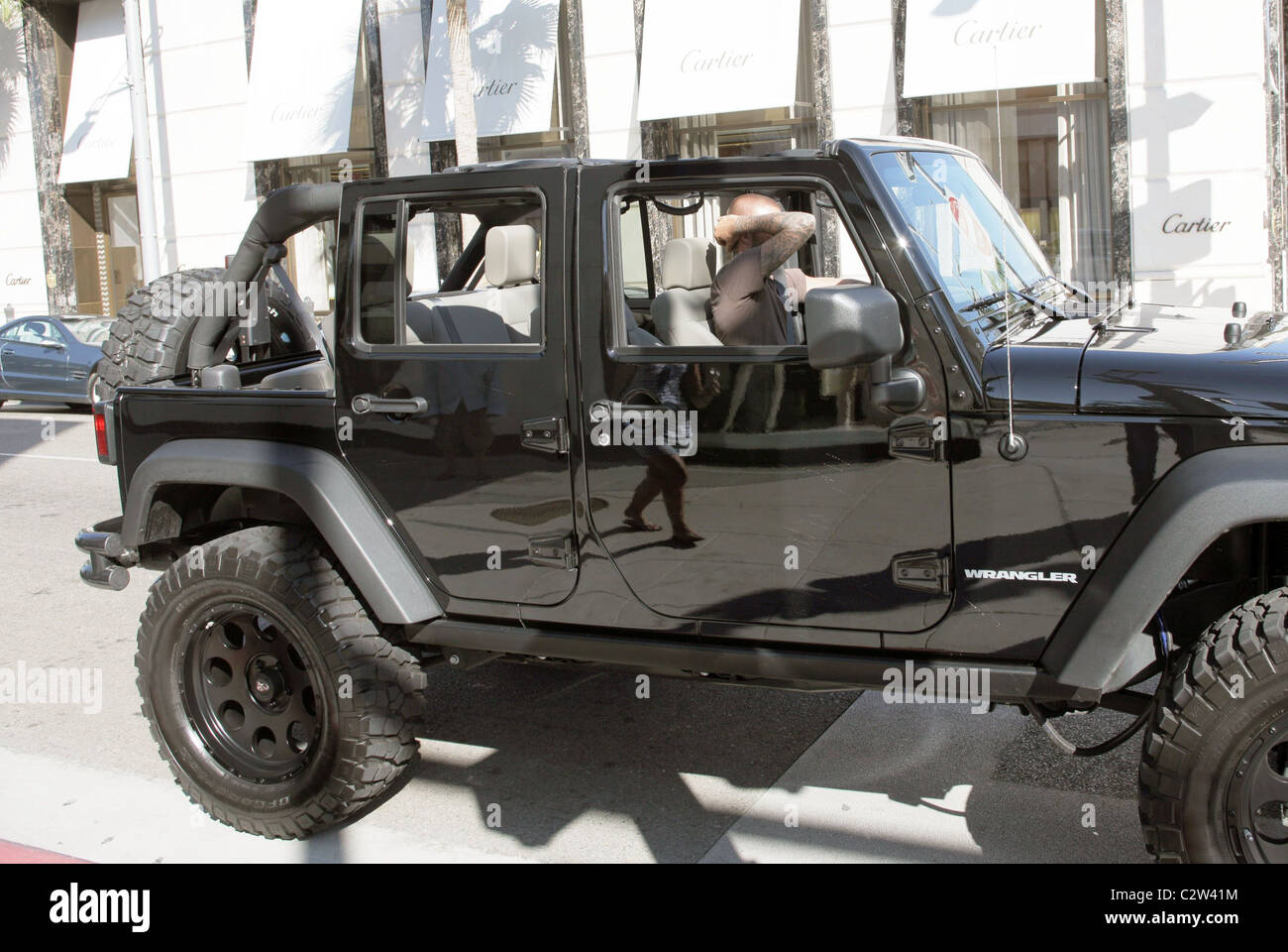 David Beckham covers his face as drives his custom Jeep through ...