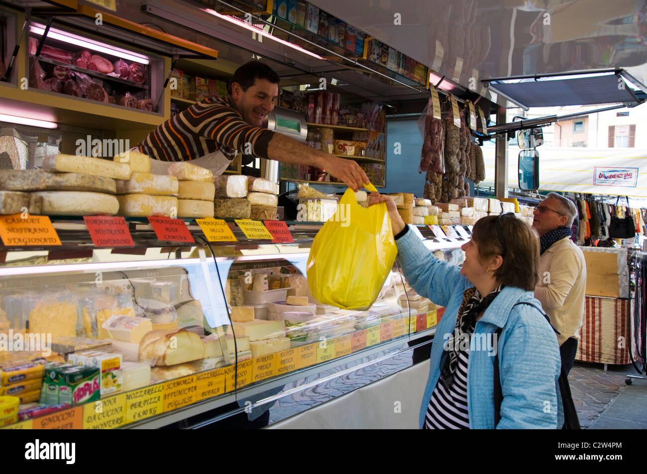 Customer at a mobile cheese and cold salami stall in marketplace in Iseo - Stock Image