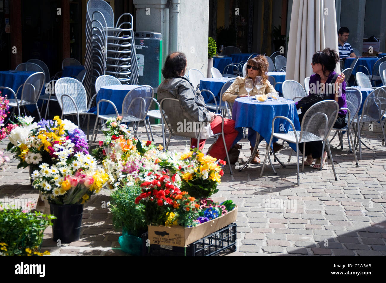 People drink and chat outside a cafe in the marketplace in Iseo Lake Iseo Italy - Stock Image