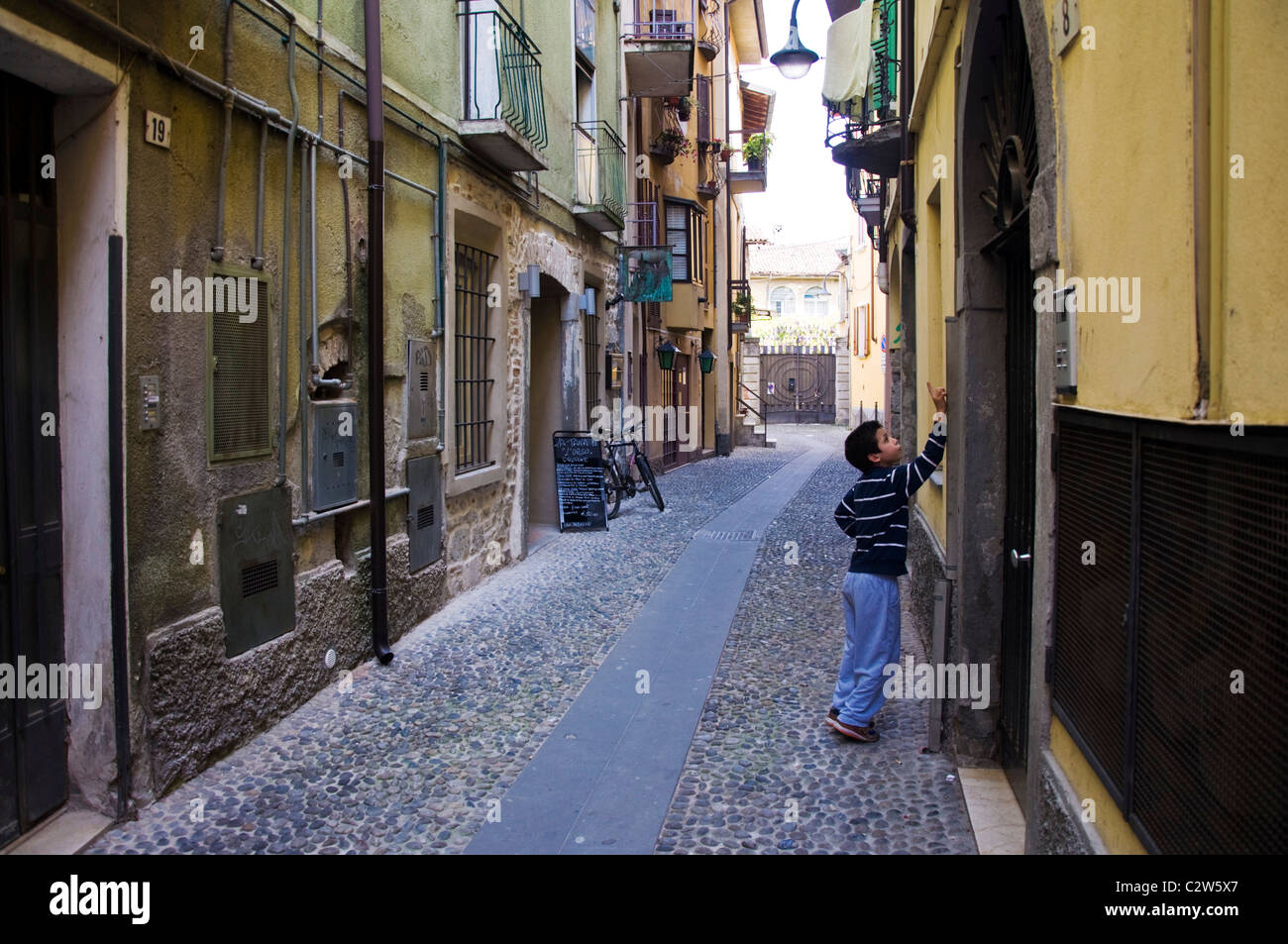 Young boy rings on a doorbell in a narrow lane in the town Iseo Lake Iseo Italy - Stock Image