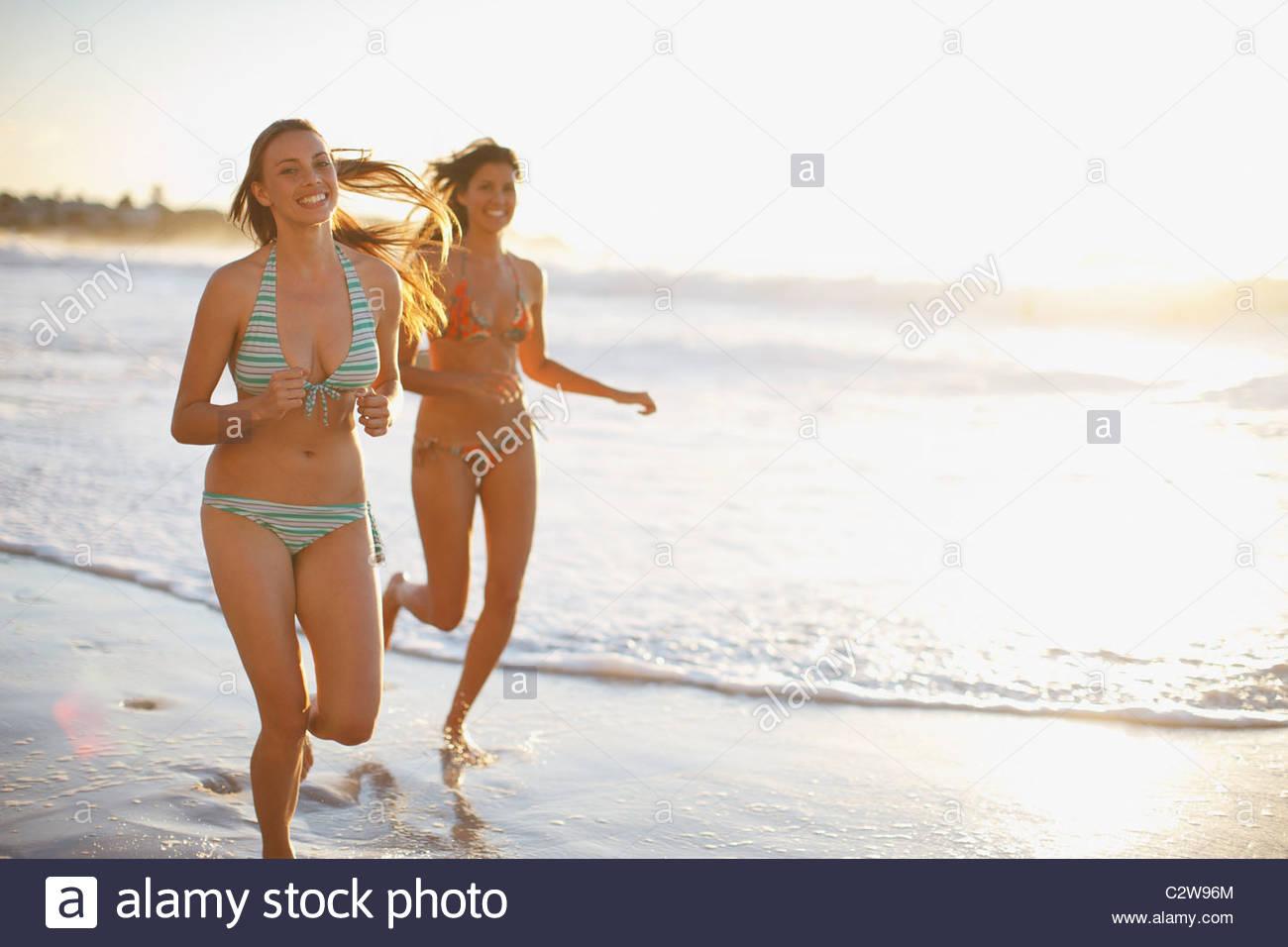Friends in bikinis running on beach - Stock Image
