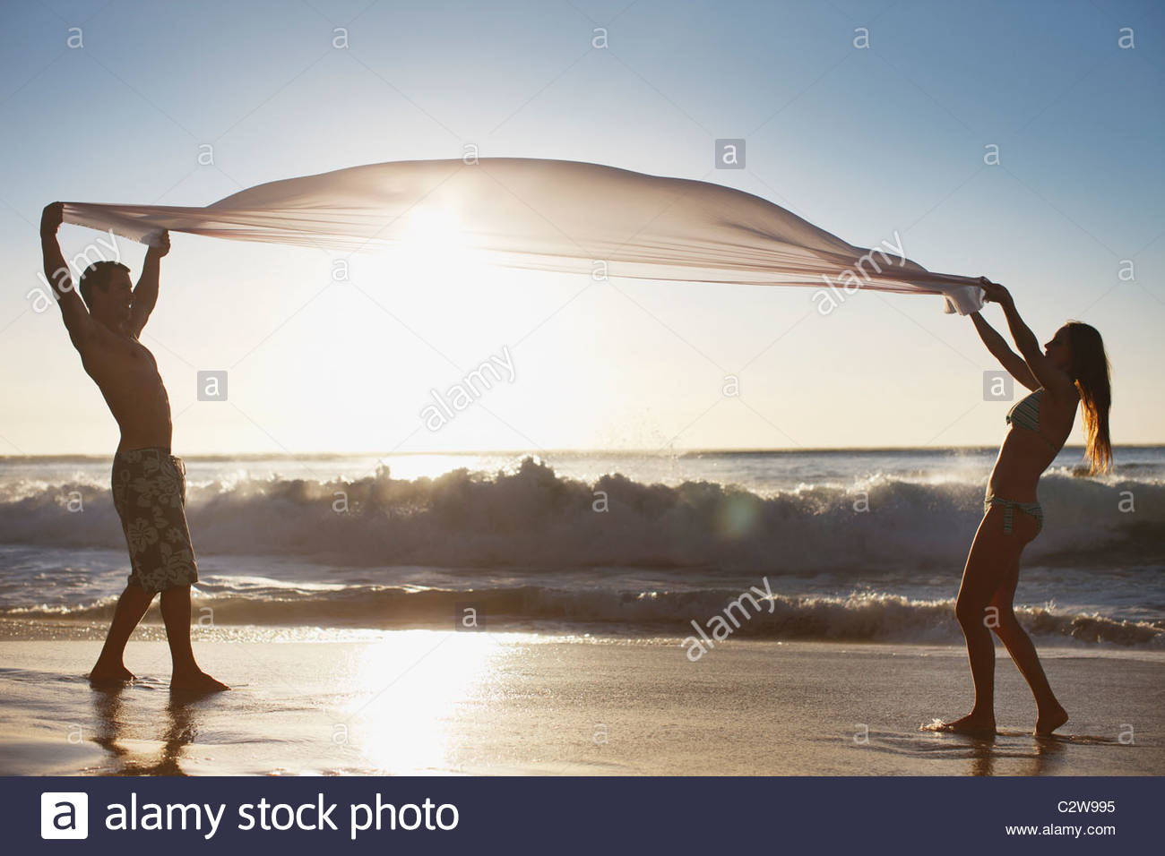 Couple standing on beach and holding fabric - Stock Image