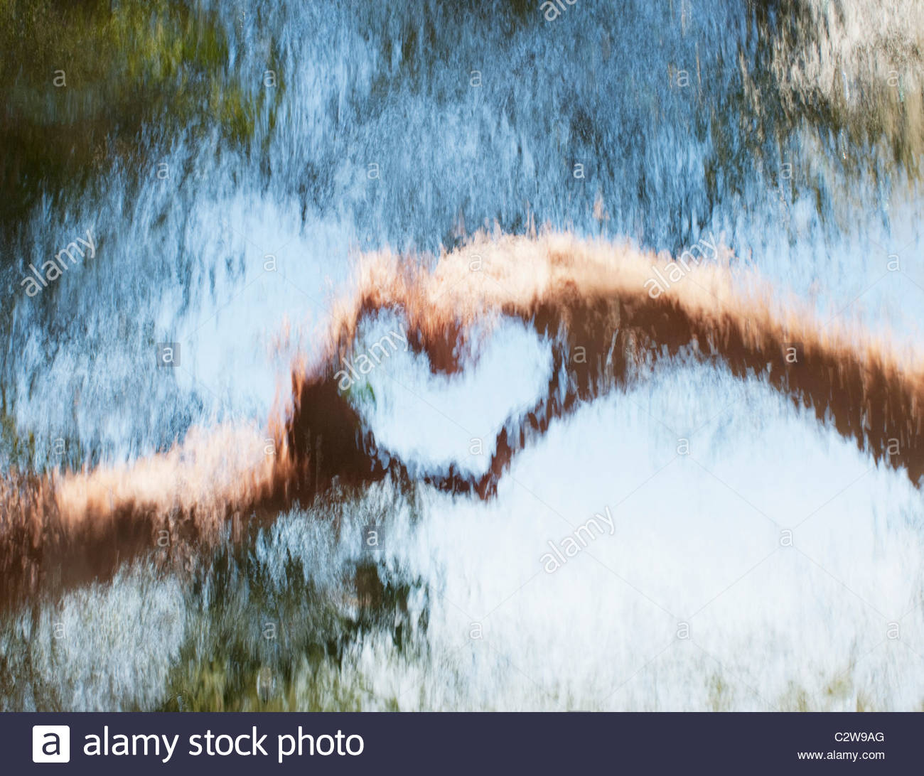 Hands making heart-shape behind glass - Stock Image