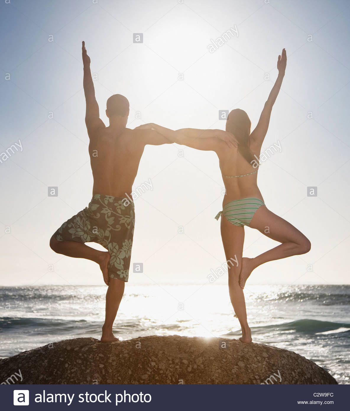 Couple balancing on one foot together at beach Stock Photo